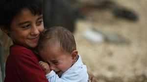 Refugee boy holds his sister outside the family tent
