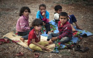 syrian refugee children sitting on a blanket