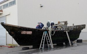 Coast guard officials investigate a wooden boat at Fukui port in western Japan after the ship was found drifting off the coast Photo: JiJi Press/AFP/Getty