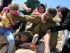 A Palestinian girl and women figth to free a Palestinian boy (bottom) held by an Israeli soldier (C) during clashes between Israeli security forces and Palestinian protesters following a march against Palestinian land confiscation to expand the nearby Jewish Hallamish settlement on August 28, 2015 in the West Bank village of Nabi Saleh near Ramallah. AFP PHOTO / ABBAS MOMANI