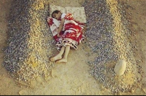 HEARTBREAKING: A Syrian boy sleeps between the graves of his dead parents. Photo: JNews).