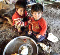 Syria: Two little boys on the dirt floor with a bowl of food. (Photo: Google).