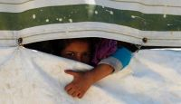 Syrian child peeps through a tent at Ain al-Helweh refugee camp. (Photo: UNICEF)