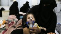 A Yemeni woman helps her malnourished child to breathe at a therapeutic feeding centre