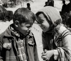 Two children giggle as they talk. (Photo/ quote: Thana Faroq).