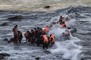 Dragged to safety: Refugees and migrants try to reach the shore of the Greek island of Lesbos today, battling against the rough sea. Photo: Daily Mail).