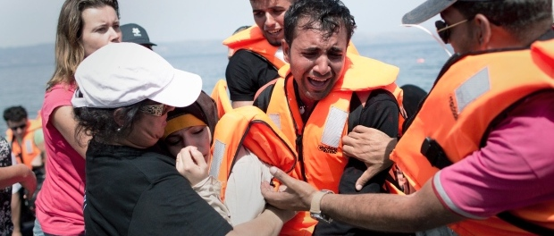 A volunteer helps a Syrian woman that collapsed while her husband cries as they arrive aboard a dinghy after crossing from Turkey, on the island of Lesbos, Greece, Monday, Sept. 7, 2015. (Petros Giannakouris/AP).