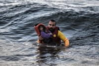 Saviour: A lifeguard rescues a child as a boat with refugees and migrants sunk, while crossing the Aegean sea from Turkey to the Greek island of Lesbos. Photo: Daily Mail).