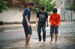 Children enjoy a downpour on Aug. 11, 2015. (Photo/ quote: Thana Faroq).