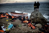 Survivors: Two men look out to sea after the terrifying ordeal, on the Greek island of Lesbos, after a boat carrying migrants and refugees sank. Photo: Daily Mail);