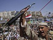 A Yemeni army officer holds up his AK-47 during anti-government protests earlier this week. The Foreign Office said only a 'small core' of staff will remain in the country, and it urged other British nationals to leave (AP)