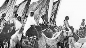 Abdul Aziz al-Saud's militia of Bedouin warriors, a ferocious brigand named Uthman al-Mudayiqi. The flags date the photo to second Saudi state under Abdul Aziz