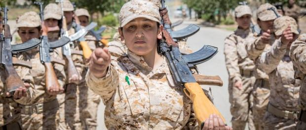 SULAYMANIYAH, IRAQ - JULY 29. 2014: Women Peshmerga of the 2nd Battalion perform a military march during a military exercise in Sulaymaniyah, Iraq. Dressed head-to-toe in army fatigues with rifles over their shoulders, these are the female fighters of the Peshmerga ready to lay down their lives in combat against the Islamic State. In the scorching heat on the outskirts of Sulaymaniyah, Kurdistan, they carry out routine exercises and look no different from other Kurdish fighters. The 2nd Battalion consists of 550 mothers, sisters and daughters and is led by Colonel Nahida Ahmad Rashid. (PHOTOGRAPH BY Vianney Le Caer / Pacific Press).