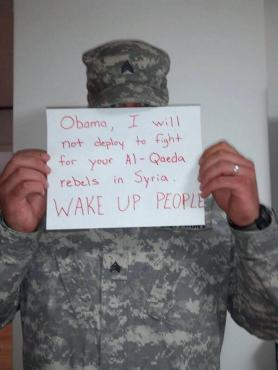 A US solider being deployed to Syria holds up a sign. (Photo: Global Research).