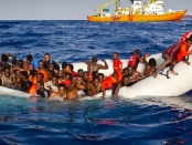 Refugees ask for help from a dinghy boat as they are approached by the SOS Mediterranee's ship Aquarius on Sunday. The UNHCR said up to 500 people are feared dead in the sinking. (Patrick Bar/SOS Mediterranee/Associated Press)