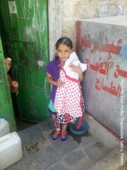 Yemen. A little girl holding her new dress from YA.
