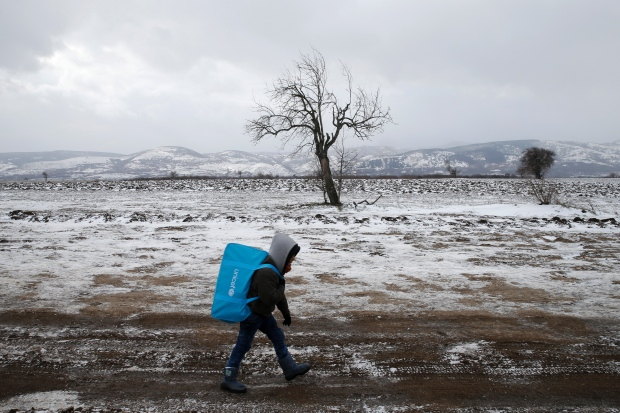 A migrant child walks through a frozen field after crossing the border from Macedonia, near the village of Miratovac, Serbia, January 18, 2016. (Marko Djurica/Reuters)