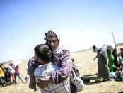 "A Syrian Kurd carries an elderly woman after crossing the border between Syria and Turkey near the southeastern town of Suruc in Sanliurfa province, on September 20, 2014. Several thousand Syrian Kurds began crossing into Turkey on September 19 fleeing Islamic State fighters who advanced into their villages, prompting warnings of massacres from Kurdish leaders. Turkey on September 19 reopened its border with Syria to Kurds fleeing Islamic State (IS) militants, saying a ""worst-case scenario"" could drive as many as 100,000 more refugees into the country. AFP PHOTO/BULENT KILICBULENT KILIC/AFP/Getty Images"