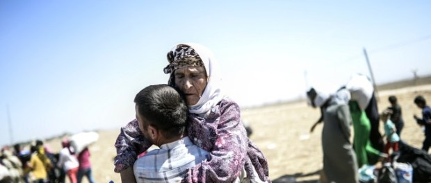 A Syrian Kurd carries an elderly woman after crossing the border between Syria and Turkey near the southeastern town of Suruc in Sanliurfa province, on September 20, 2014. Several thousand Syrian Kurds began crossing into Turkey on September 19 fleeing Islamic State fighters who advanced into their villages, prompting warnings of massacres from Kurdish leaders. Turkey on September 19 reopened its border with Syria to Kurds fleeing Islamic State (IS) militants, saying a