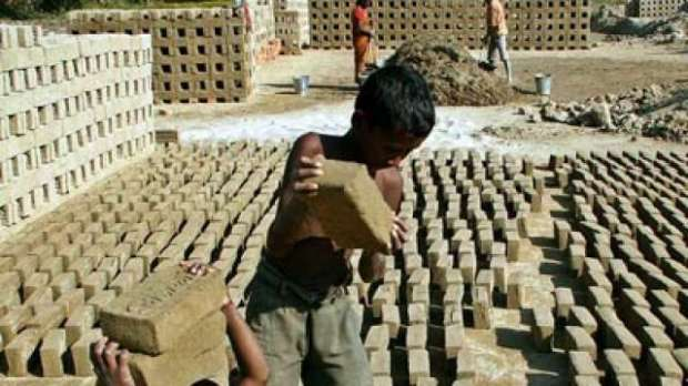 A young boy working in a brick making factory in Maharashtra India.