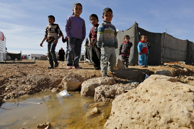 Syrian refugee children pose as they play near their families' residence at Al Zaatari refugee camp in the Jordanian city of Mafraq, near the border with Syria, January 30, 2016. (Muhammad Hamed/Reuters)