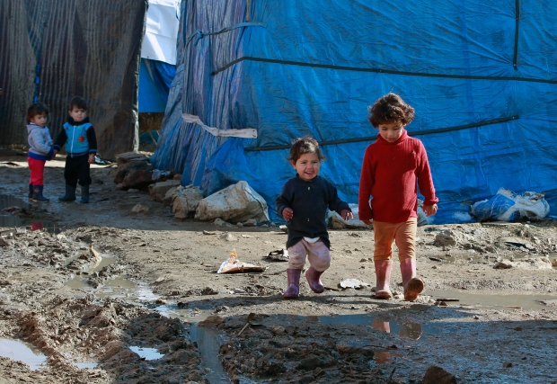 Syrian refugee children walk outside their family tents at a Syrian refugee camp, in the eastern town of Kab Elias, Lebanon, Wednesday, Jan. 27, 2016. (Bilal Hussein/AP)