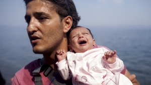 A Syrian refugee from Aleppo holds his one month old daughter moments after arriving on a dinghy on the Greek island of Lesbos, September 3, 2015. Credit: Photo by Dimitris Michalakis/Reuters.