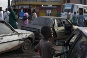 A young boy from a Quranic school begs for change from a driver stopped at a gas station, in the Medina Gounass suburb of Dakar, Senegal, Sept. 24, 2013. © 2013 Rebecca Blackwell/Associated Press