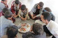 Yemen: Inside Your Ability's facility, where children are eating dinner with a staff member.