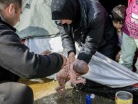 A mother forced to wash infant in dirty puddle at Idomeni camp in Greece. (Photo: Iran Daily).