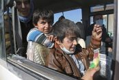 Yazidi boys, suffering from several infections from mosquito bites while held by ISIL, wait with their mother inside a bus outside the northern Iraqi city of Kirkuk after having been freed by the extremists. Bram Janssen/AP Photo