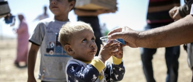 "A Syrian Kurd child holds a glass of water after he crossed the border between Syria and Turkey near the southeastern town of Suruc in Sanliurfa province, on September 20, 2014. Several thousand Syrian Kurds began crossing into Turkey on September 19 fleeing Islamic State fighters who advanced into their villages, prompting warnings of massacres from Kurdish leaders. Turkey on September 19 reopened its border with Syria to Kurds fleeing Islamic State (IS) militants, saying a ""worst-case scenario"" could drive as many as 100,000 more refugees into the country. AFP PHOTO/BULENT KILICBULENT KILIC/AFP/Getty Images"