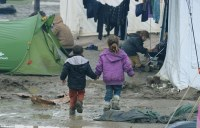 Two refugee children walk through the muddy field at the makeshift migrant camp in Idomeni which is suffering an outbreak of infection