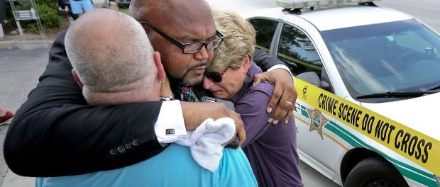 Kelvin Cobaris, a local clergyman, consoles Orlando city Commissioner Patty Sheehan, right. The Pulse nightclub in Orlando is considered to be the worst mass shooting in American history. 5o dead and at least 53 other people were hospitalized, most in critical condition, officials said. A surgeon at Orlando Regional Medical Center said the death toll was likely to climb. (Photo: Gazette, credit: Daily News).