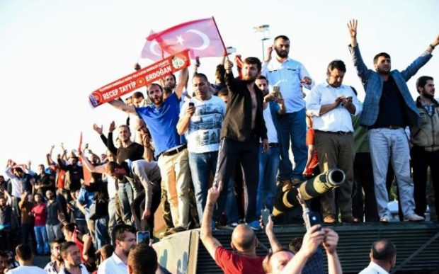 People stand and celebrate on an army tank after taking over a military position on the Bosphorus bridge in Istanbul on July 16, 2016. (Photo: BULENT KILIC/ AFP).
