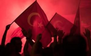 People shout slogans and hold Turkish national flags during a demonstration CREDIT:MARIUS BECKER