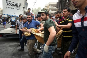 Iraqi men carry on July 4, 2016 a body of a victim, who died in a suicide-bombing attack which took place a day earlier, in Baghdad's Karrada neighbourhood.