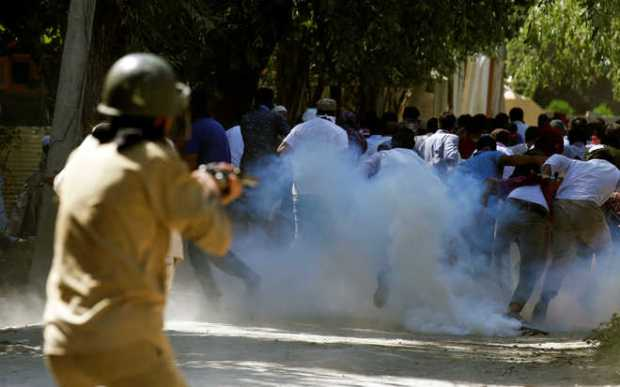 Protesters run away as a policeman fires tear gas during a protest in Srinagar on August 5, 2016. (Photo: Reuters).